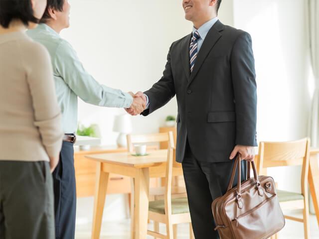 男性と握手する不動産スタッフ
